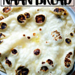 A stack of homemade, yeasted naan on a plate.