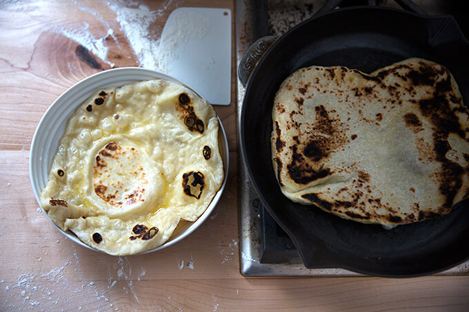 A skillet of naan being cooked aside a freshly cooked naan in a bowl.
