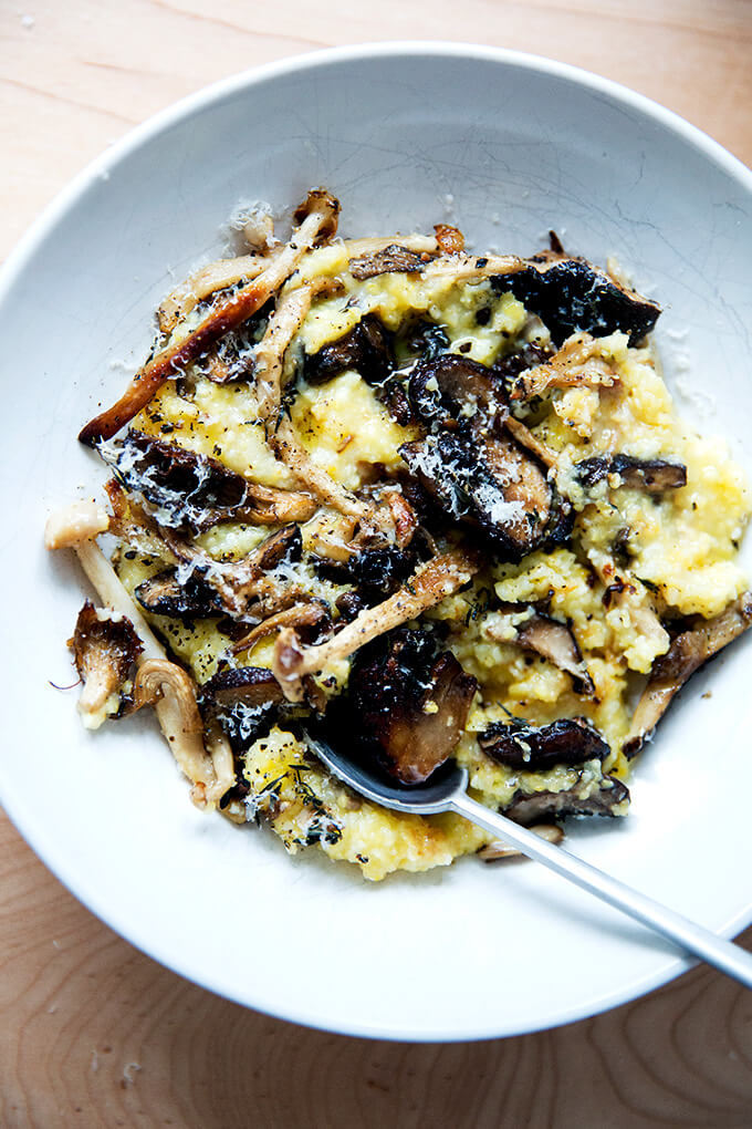 A bowl of roasted mushroom polenta bake with a spoon in it.