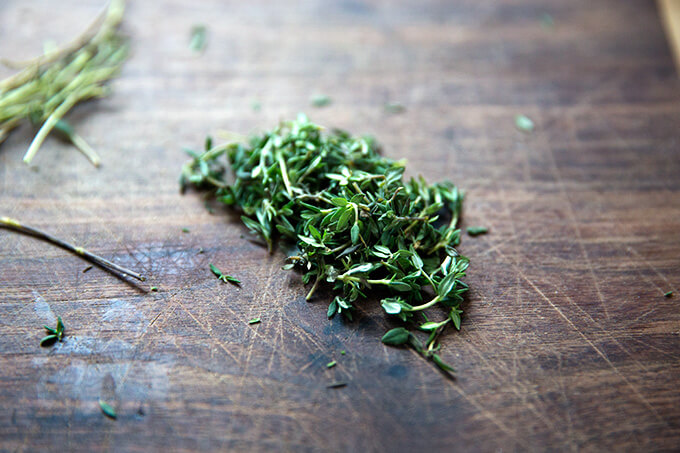 Thyme leaves on a cutting board.