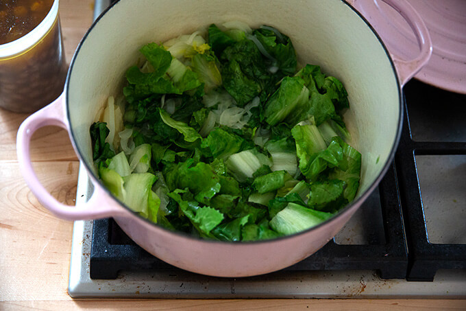 A Dutch oven filled with sautéed onions and wilted escarole.
