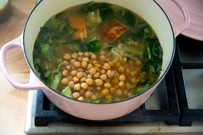 A Dutch oven filled with escarole and chickpea soup ready to simmer.