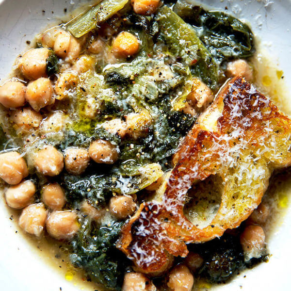 A bowl of chickpea and escarole soup with toasty bread.