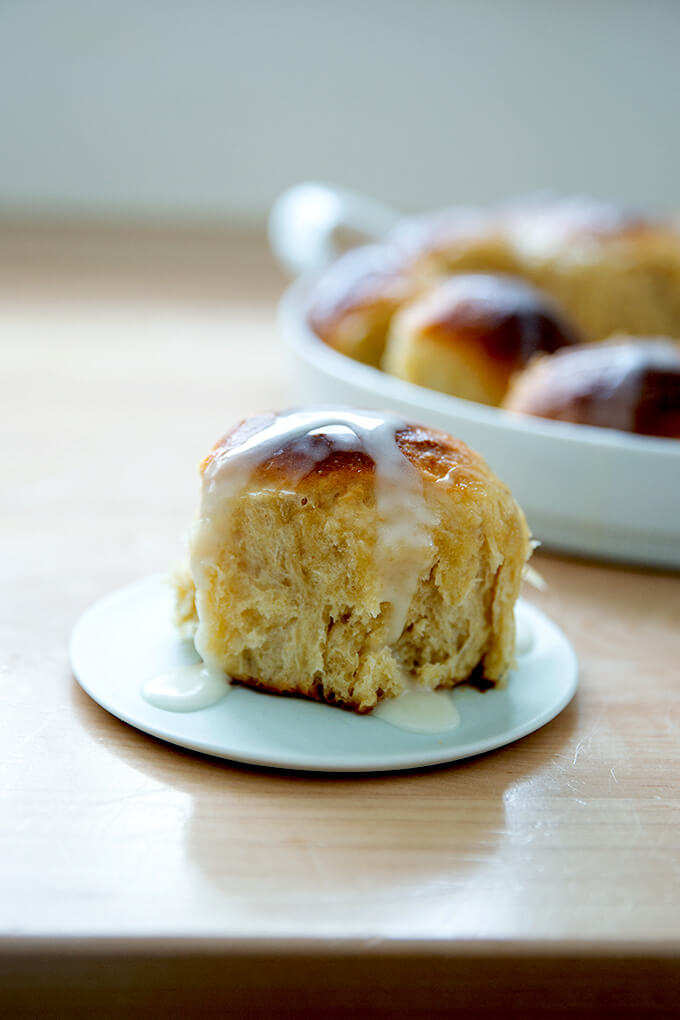 Individual hot cross bun on a plate.