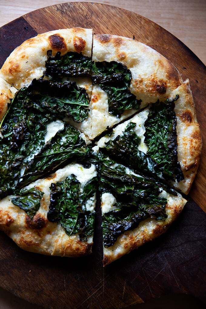 Sourdough kale and creme fraiche pizza on a board, cut into pieces.