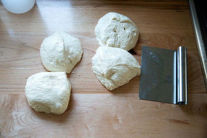 Portioned sourdough pizza dough aside a bench scraper.