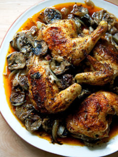 A platter of roast chicken with dates and artichoke hearts.
