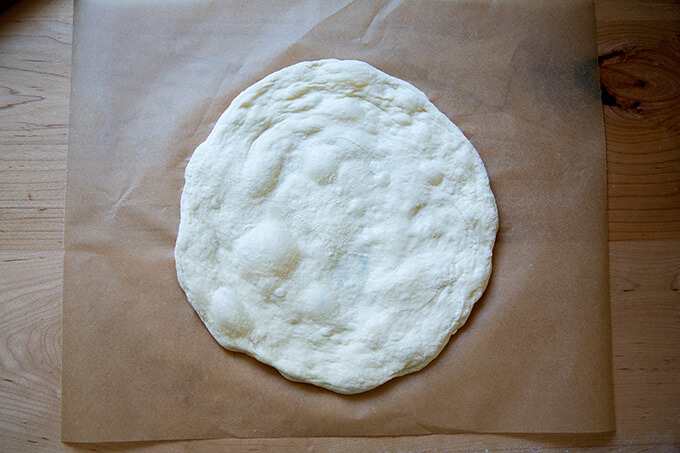 Stretched round of sourdough pizza on parchment paper.