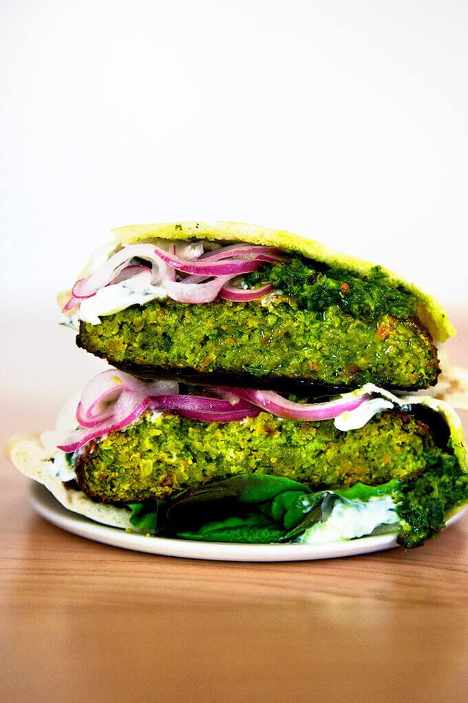 A halved falafel burger on a plate.