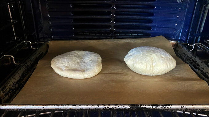 Two pita cooking on a non-preheated sheet pan.
