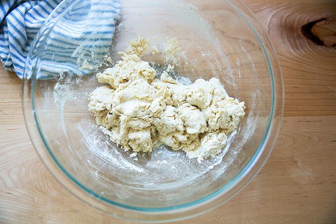 A shaggy pita bread dough in a large bowl.