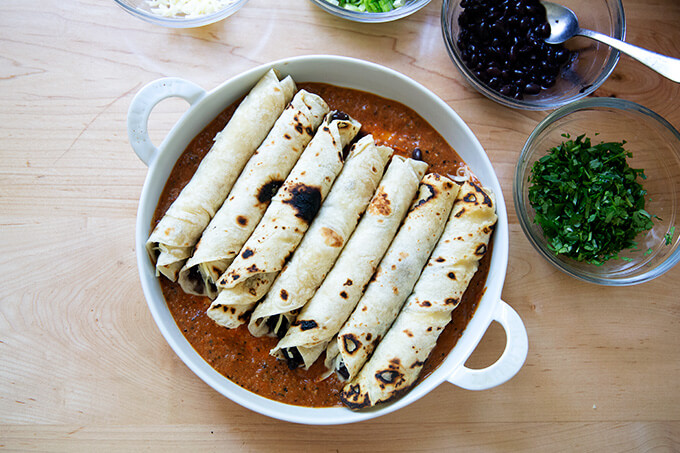 A baking dish filled with tortillas rolled with black beans and Monterey Jack cheese.