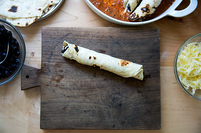 A single rolled flour tortilla filled with black beans and Monterey Jack cheese.