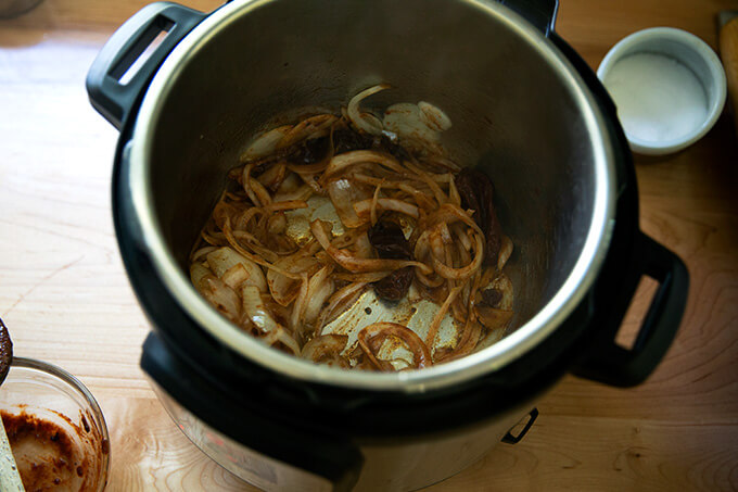 An Instant Pot filled with sautéed onions and chipotle in adobo sauce.