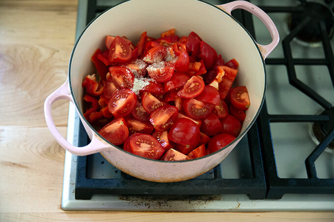 A large pot filled with tomatoes, peppers, water, and salt.