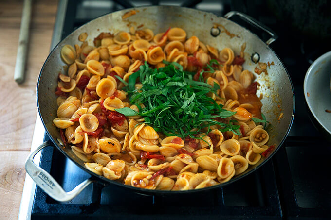 A skillet of pasta on the stovetop with basil added.
