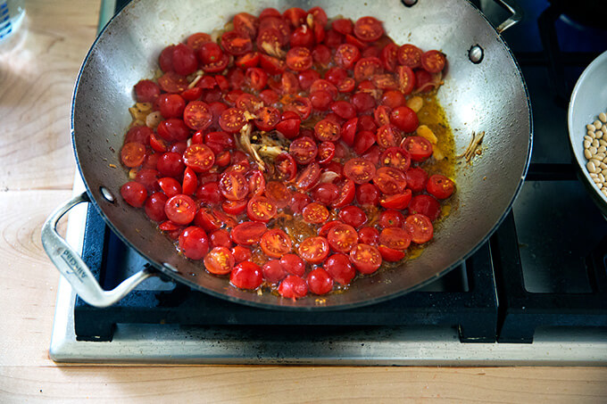 A skillet on the stovetop with shallots, garlic, olive oil, and tomatoes.