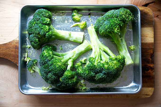 Two halved heads of broccoli on a sheet pan.