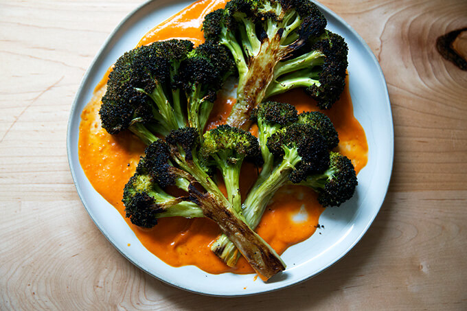 Roasted broccoli halves on a plate spread with tomato sauce.