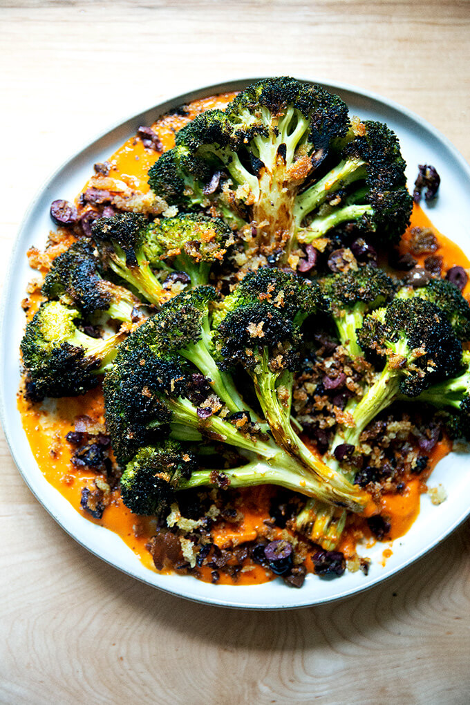 A plate of roasted broccoli steaks on tomato sauce topped with olive bread crumbs.