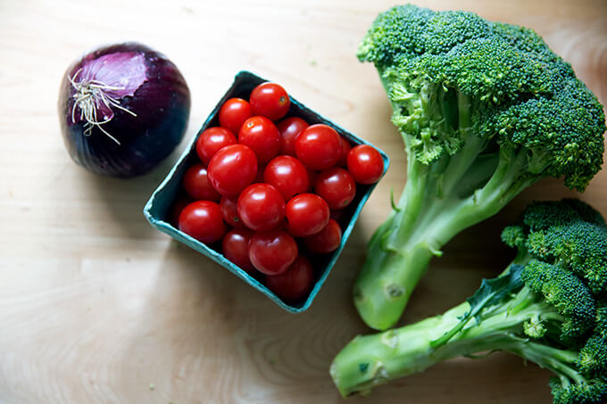 An onion, pint of cherry tomatoes and two heads of broccoli on a kitchen counter.