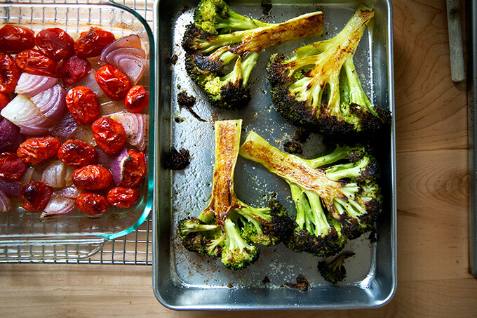 Two pans: one holding roasted tomatoes and onions; the other holding roasted broccoli.