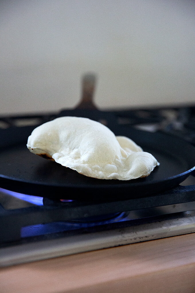 A sourdough flour tortilla cooking in a skillet stovetop.