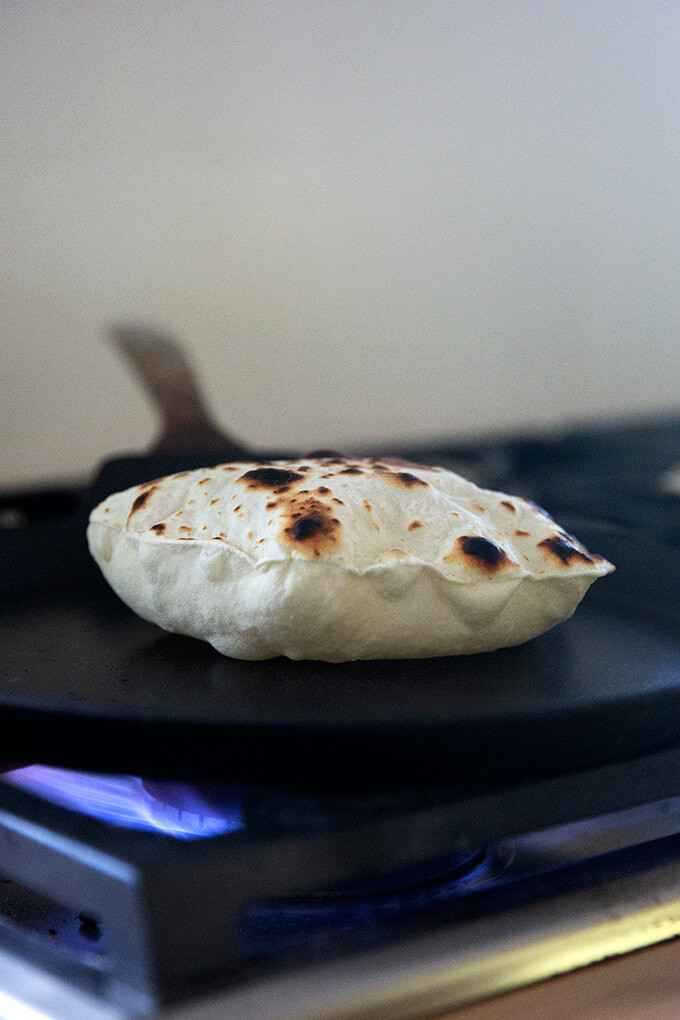 A sourdough flour tortilla cooking in a skillet stovetop.