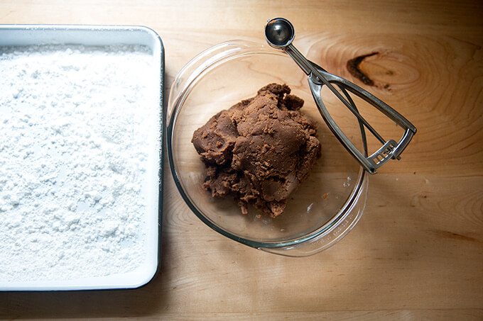 "The ""batter"" for the rum balls in a bowl aside a powdered-sugared filled tray."