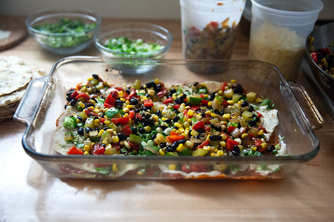 Layering the enchilada casserole with tortillas and summer vegetables.