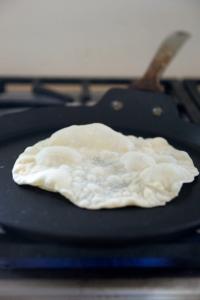 A sourdough tortilla cooking stovetop in a skillet.