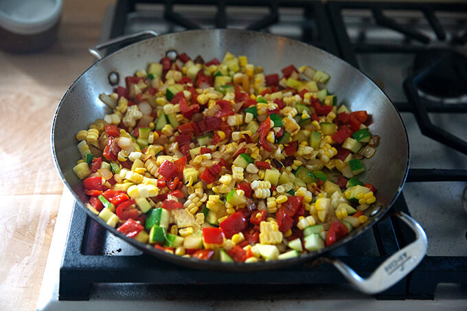 A skillet on the stovetop with sautéed summer vegetables.