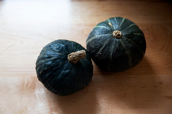 Two Kabocha squash on a countertop.