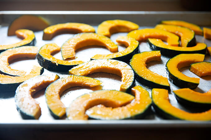 Sliced kobacha squash tossed with olive oil and salt on a sheet pan.
