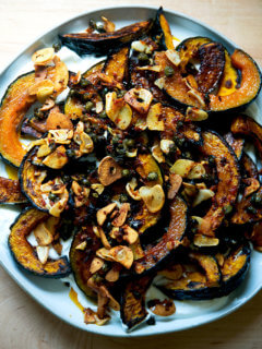 A plate of roasted Kabocha squash atop lemony yogurt sauce and sizzling garlic, capers, and Calabrian chili paste.