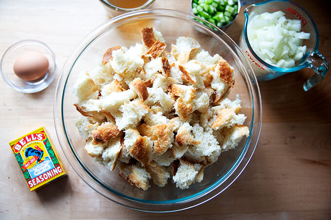 A bowl of cubed bread and ingredients to make a classic bread stuffing.