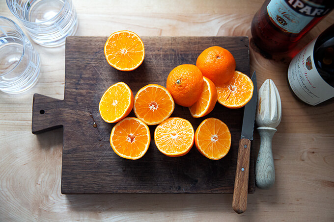 Halved clementines on a board.