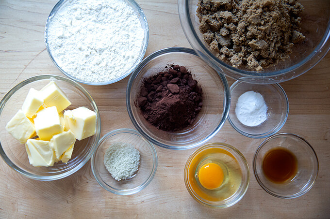 Ingredients to make chocolate sugar cookies on a work surface.