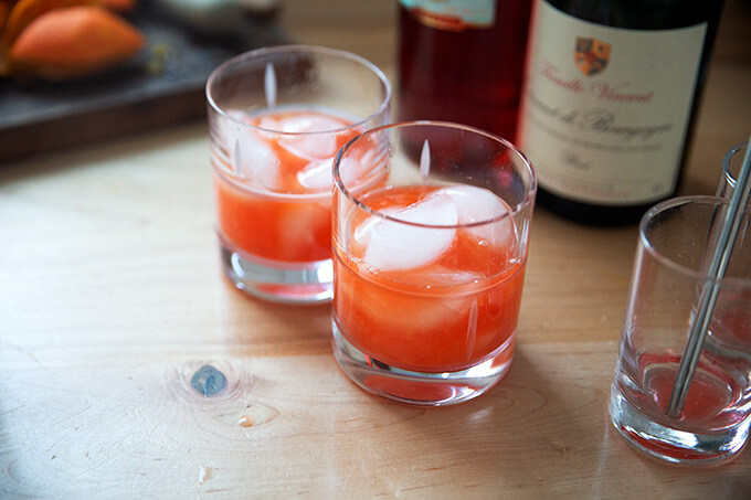 Two glasses filled with ice, fresh squeezed tangerine juice, and Campari.