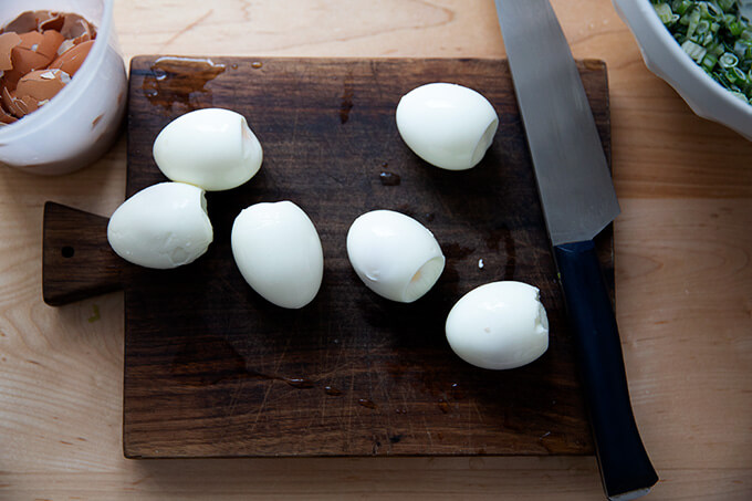 Six steamed hard boiled eggs on a board.