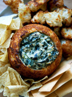 A bread bowl filled with spinach artichoke dip.
