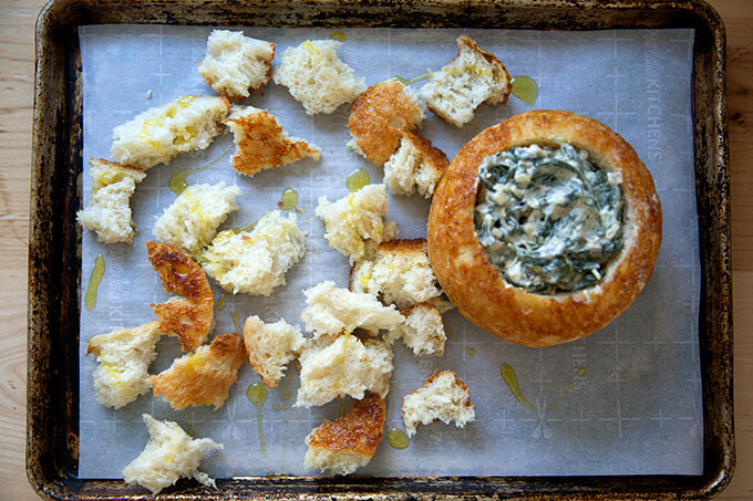 A sheet pan filled with a peasant bread bread bowl filled with spinach-artichoke dip.