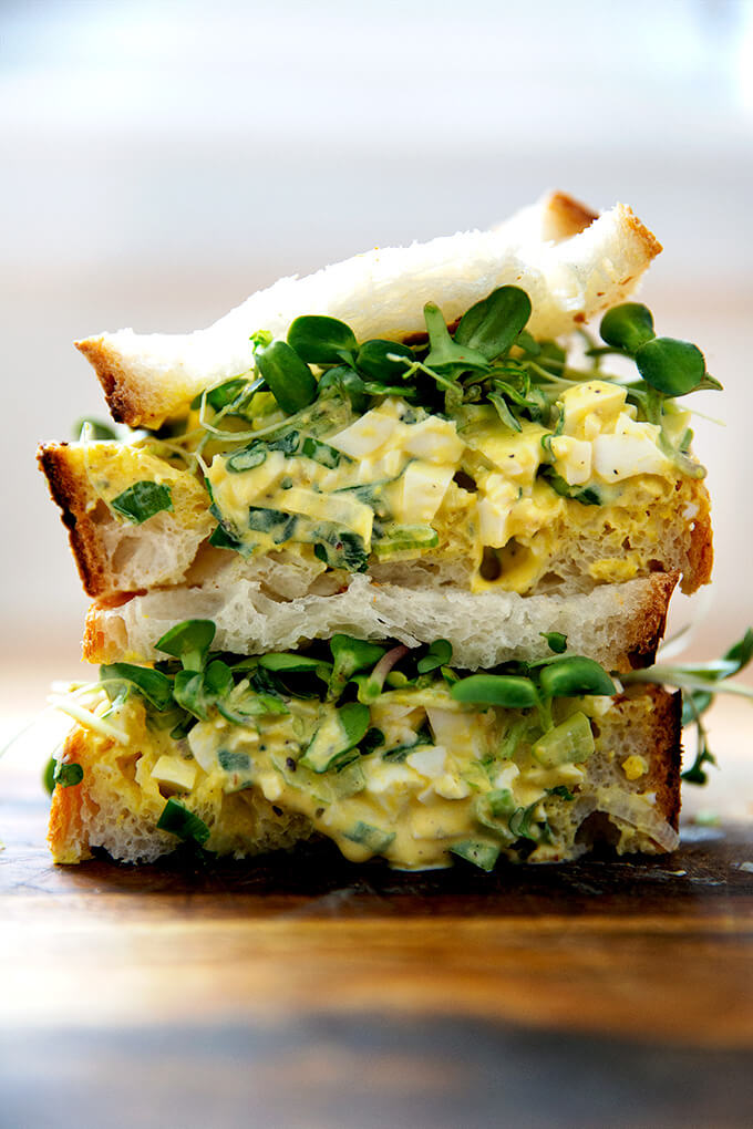 The best egg salad sandwich on a board.