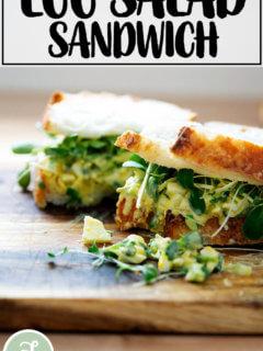 An egg salad sandwich on a board.