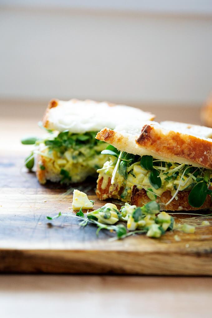 Egg salad sandwich on a board.