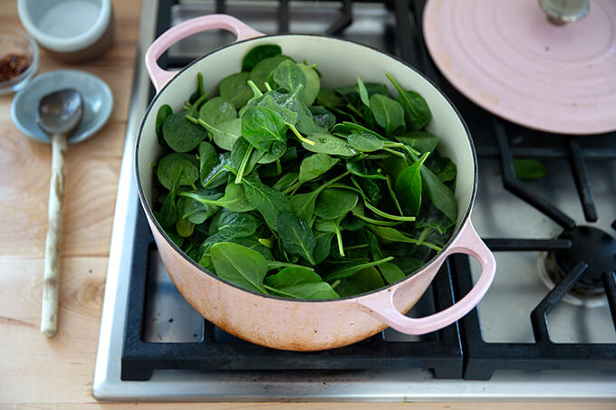 A Dutch oven filled with spinach.