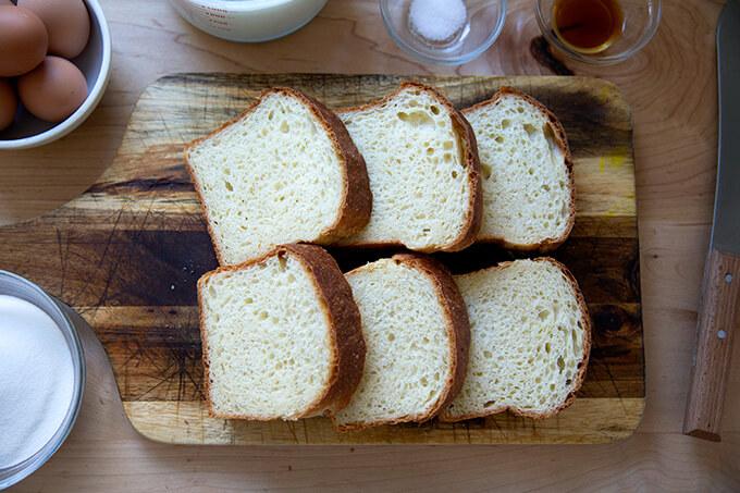 Six slices of brioche on a cutting board.
