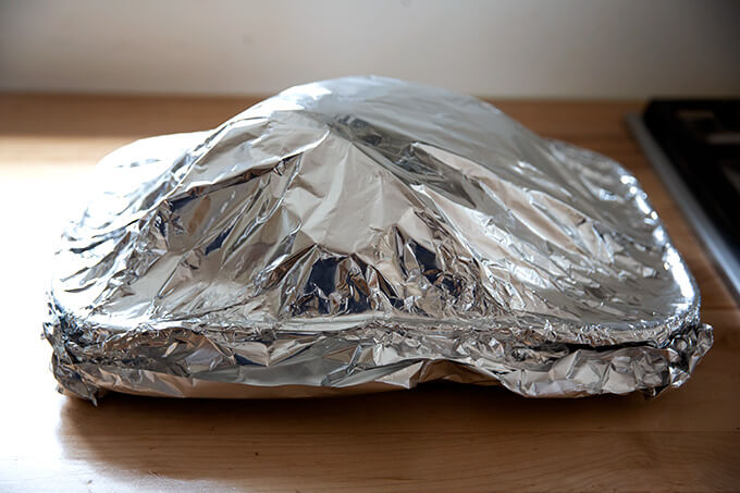 A roasting pan holding a ham, covered in foil.