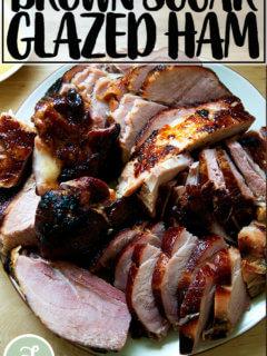 A carved brown sugar glazed ham on a platter.