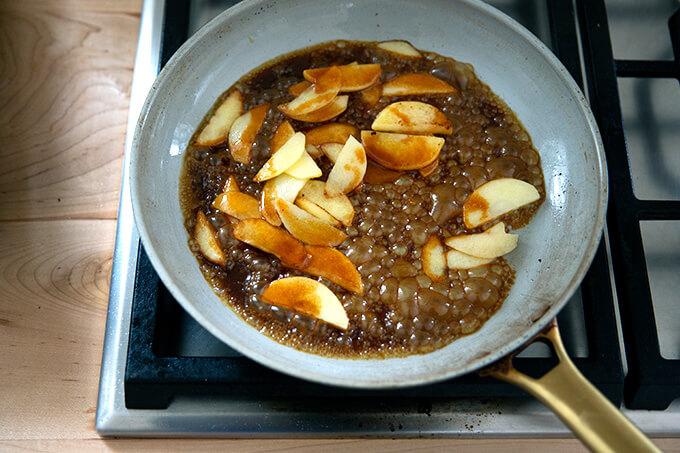A sauté pan filled with apples and caramel sauce.